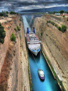klein bootje trekt schip door geul